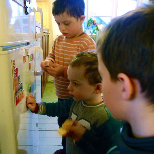 Leo, Tom och Axel klär kylen med bokstäver och siffror.