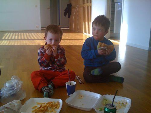 Bröderna brothers äter hamburgare i ett aldrig så tomt vardagsrum